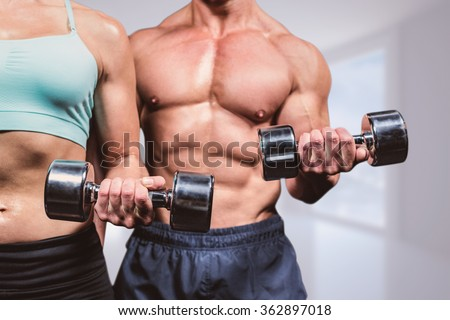Midsection of woman and man exercising with dumbbells against bright white corridor with windows - stock photo