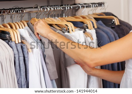 Midsection of woman choosing shirt from rack in clothing store - stock photo