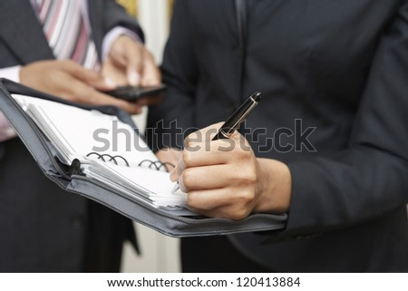 Midsection of woman taking down notes with man using cellphone in background