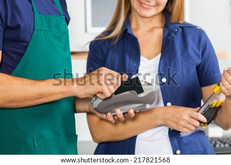 Midsection of worker swiping credit card with woman holding screwdriver set in hardware store - stock photo