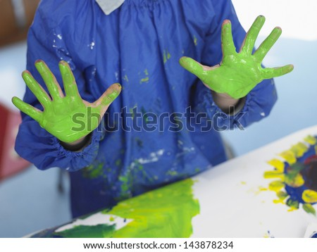 Midsection of young boy with green painted hands in art class - stock photo