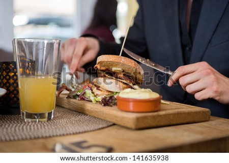 Midsection of young businessman having sandwich in restaurant - stock photo