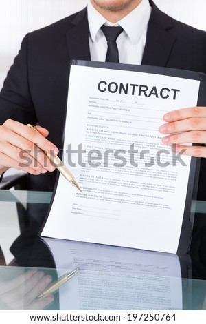 Midsection of young businessman showing contract paper at desk in office - stock photo