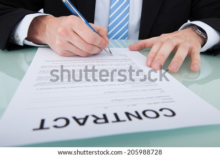 Midsection of young businessman signing contract paper at office desk - stock photo