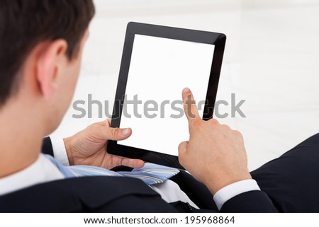 Midsection of young businessman using digital tablet in office - stock photo