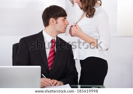 Midsection of young businesswoman seducing boss in office - stock photo