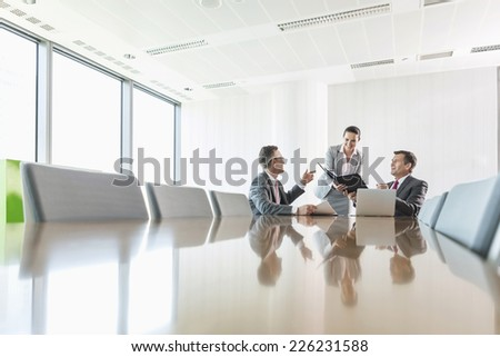 Midsection of young businesswoman using copy machine in office - stock photo