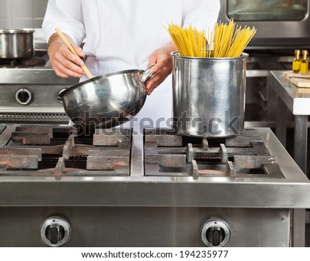 Midsection of young chef cooking spaghetti in commercial kitchen
