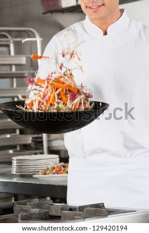 Midsection of young male chef tossing vegetables from wok in commercial kitchen - stock photo