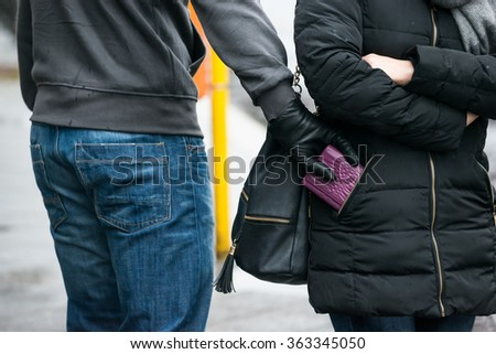 Midsection of young male robber stealing clutch from woman's jacket on street during winter - stock photo