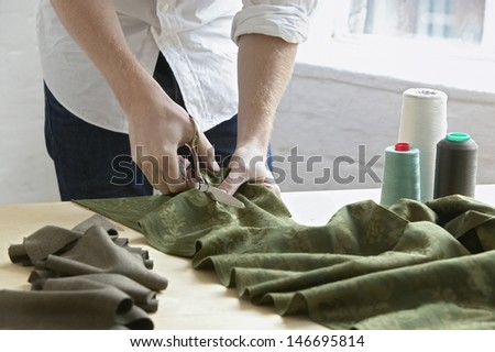 Midsection of young male tailor cutting piece of cloth at table in fashion studio