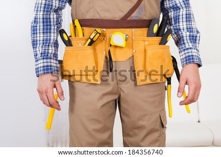 Midsection of young man wearing tool belt at home - stock photo