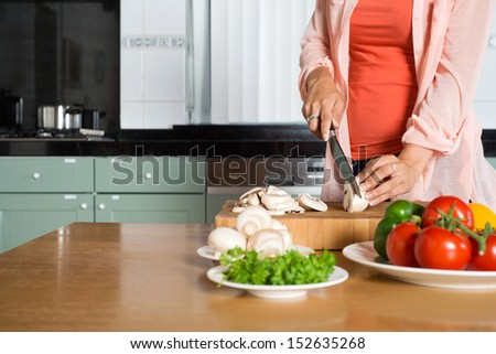Midsection of young woman cutting vegetables on wooden chopping board at kitchen counter - stock photo
