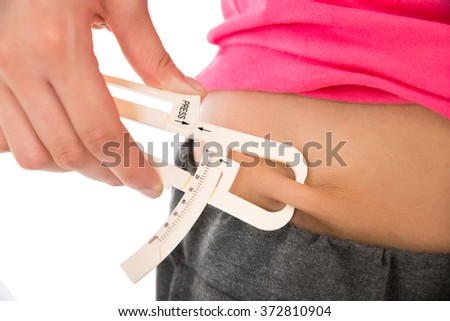 Midsection of young woman measuring fats with caliper against white background - stock photo