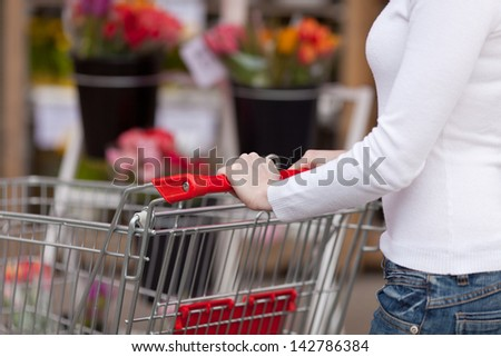 Midsection of young woman pushing shopping cart in supermarket - stock photo