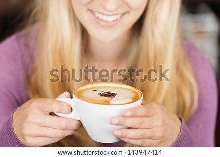 Midsection of young woman smiling while holding coffee cup - stock photo