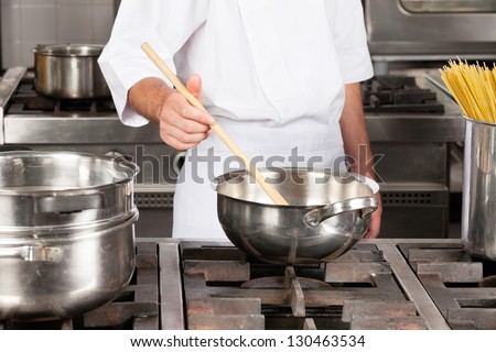 Midsection on male chef preparing food in restaurant kitchen