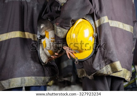 Midsection rear view of workers holding helmets at fire station - stock photo