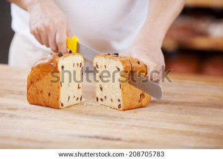 Midsection section of man cutting raisin bread loaf in bakery