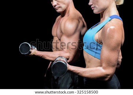 Midsection side view of man and woman lifting dumbbells against black background - stock photo