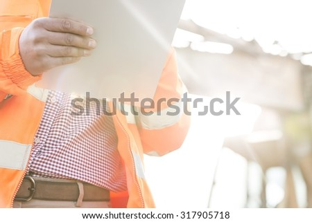 Midsection supervisor holding clipboard at construction site on sunny day - stock photo