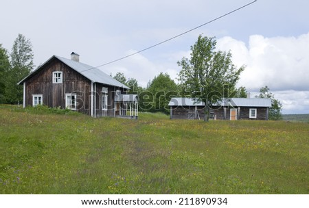 Midsummer on the farmland up North. Rural country in blossom, clouds to overcast. Elderly wooden houses on the ridge. - stock photo