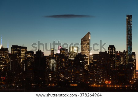 Midtown Manhattan cityscape with clear sky and one dark flat cloud during twilight in New York City. - stock photo