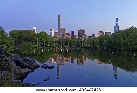 Midtown Manhattan skyline reflected from the water in Central Park.  New York, USA. Skyscrapers illuminated in the evening.