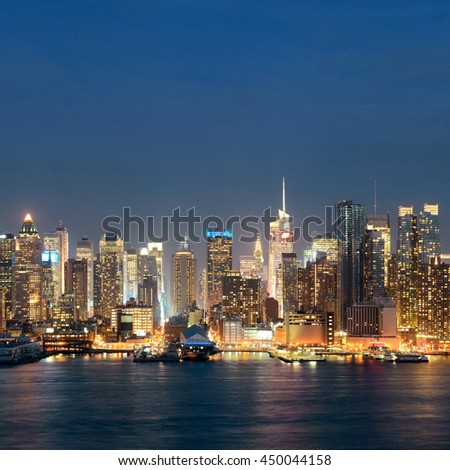 Midtown skyline over Hudson River in New York City with skyscrapers at night - stock photo