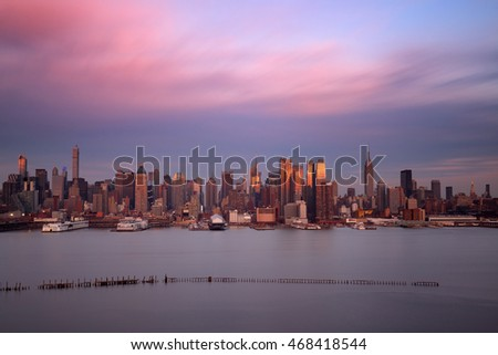 Midtown skyline over Hudson River in New York City with skyscrapers at sunset