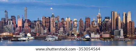 Midtown West Manhattan skyscrapers over the Hudson River. Panoramic view in early evening with moonrise and New York City skyline.