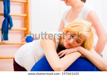 Midwife giving pregnant woman antenatal care for childbirth in practice  - stock photo