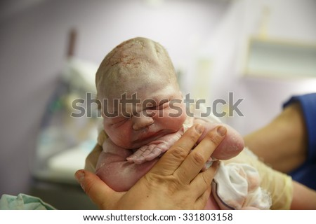 Midwife holding up a vernix covered newborn just after he was born in the delivery room, being peaceful and serene, still attached with umbilical cord. New life, birth experience concept.  - stock photo