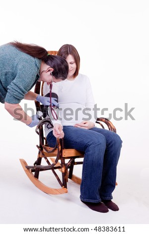 midwife taking the blood pressure of a pregnant lady - stock photo