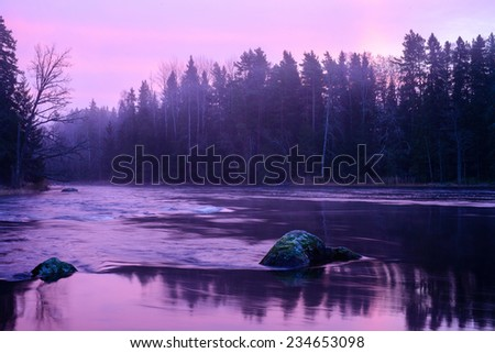 Midwinter light over flowing river before the sunrise - stock photo