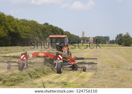 MIDWOLDE, THE NETHERLANDS - JULY 15, 2013: Haying with a tractor  with the old village church in the background