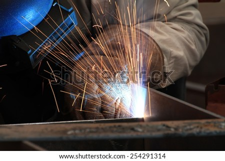MIG-MAG welder welding steel part with all safety equipment - stock photo
