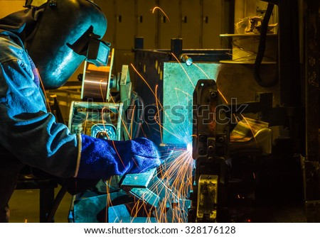 MIG welder uses torch to make sparks during manufacture of metal equipment. - stock photo