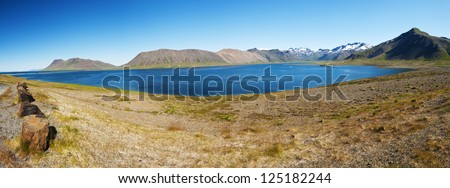 Mighty fjords rise from the sea in the Westfjords Peninsula, northwestern Iceland. Panoramic photo - stock photo