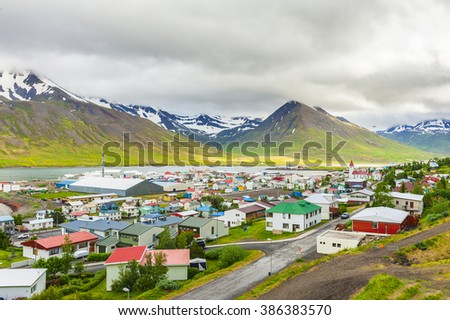 Mighty fjords with mountains covered by snow rise above the town of Olafsfjordur, Northern Iceland - stock photo