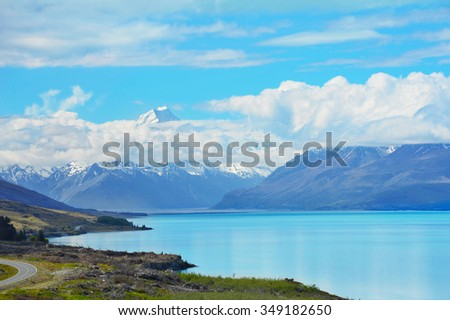 Mighty Mt. Cook is appearing from the clouds near the incredibly blue lake Pukaki at New Zealand - stock photo