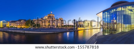 Mighty Reichstag parliament (1894), apartments and Bundeskanzleramt the German chancellery illuminated at night and reflected in the river Spree, Berlin, Germany. - stock photo