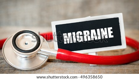 Migraine / Blackboard with word migraine and stethoscope. Medicine concept.