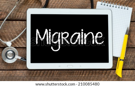 Migraine word on tablet pc on wooden background - stock photo