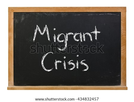 Migrant crisis written in white chalk on a black chalkboard isolated on white