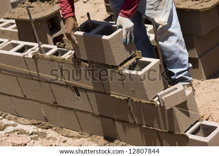Migrant worker building cinder block wall in desert setting. - stock photo
