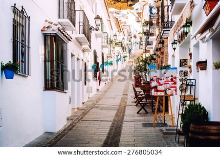 Mijas, Spain- January 05, 2014: Charming whitewashed narrow street In Mijas lined with cafes, restaurants and souvenir shops. Mijas is a lovely Andalusian white village on the Costa del Sol. Spain - stock photo