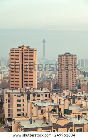 Milad Tower between two skyscrapers in the skyline of Tehran lit by the orange warm glow of sunset. - stock photo