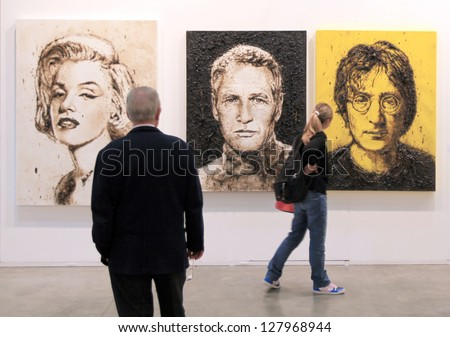 MILAN - APRIL 08: A man and a girl look at paintings representing Marylin Monroe, Paul Newman and John Lennon at MiArt, international exhibition of modern art on April 08, 2011 in Milan, Italy - stock photo