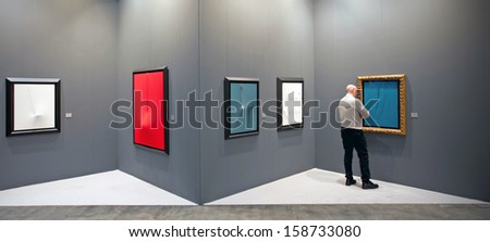 MILAN - APRIL 08: Man looks at paintings galleries during MiArt, international exhibition of modern and contemporary art on April 08, 2011 in Milan, Italy  - stock photo